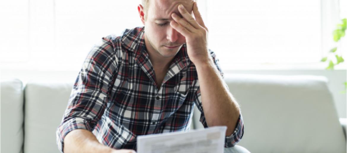 Man worried with head in hands looking at a bill