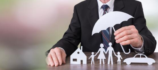 Businessman holding umbrella over investments