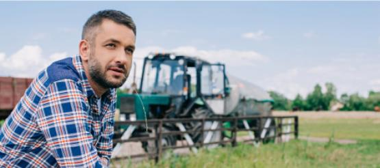 Farmer next to tractor in field