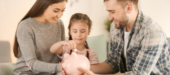 Parents with child putting money into a piggy bank