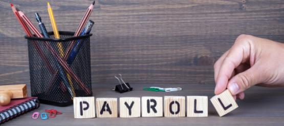 Payroll spelling in wooden blocks on a table