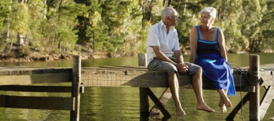 retired couple sitting on a jetty