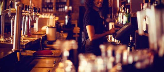 Woman serving behind bar