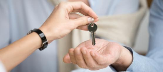 Businesswoman passing keys to businessman