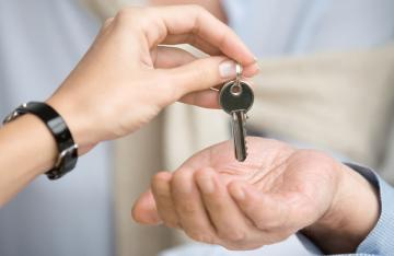 Businesswoman passing keys to businessman