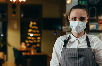 Waitress wearing mask in restaurant